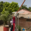 Village de Bouhinor, Casamance, Sénégal. La maison de Paul Mendy. Inspection d'un panneau photovoltaïque.